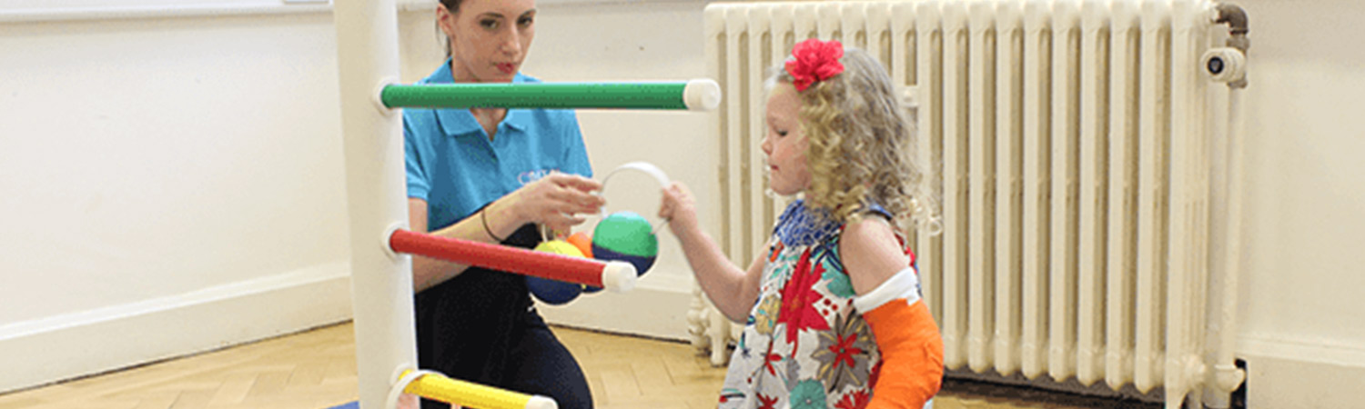 CIMT child putting hoops on a pole with their personal physiotherapist