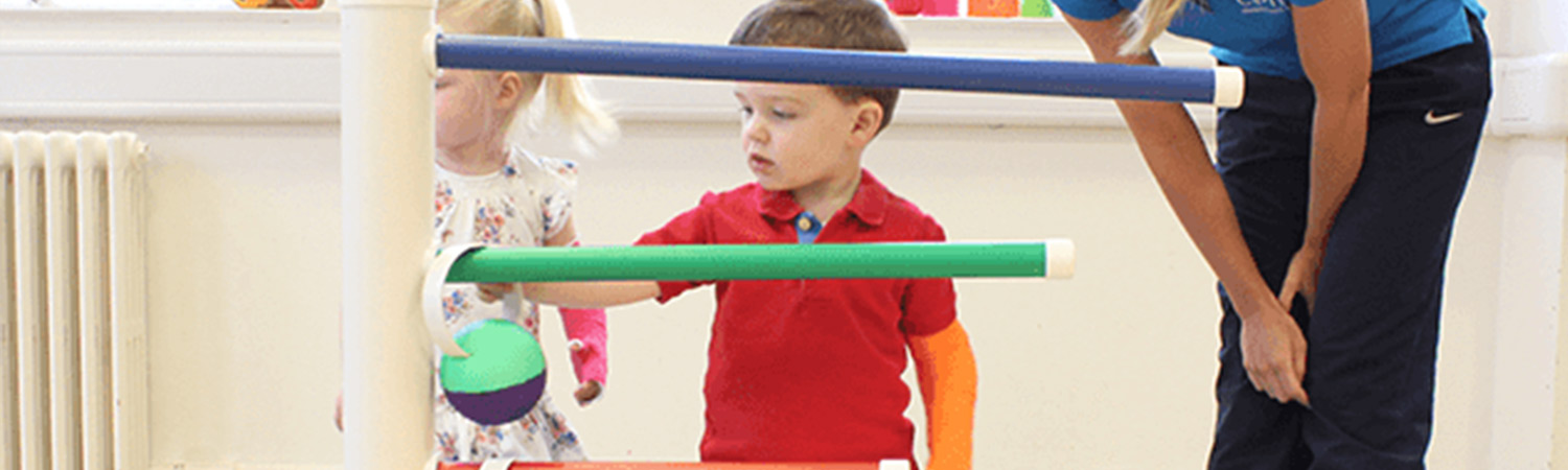 CIMT child patient sliding objects onto a pole.