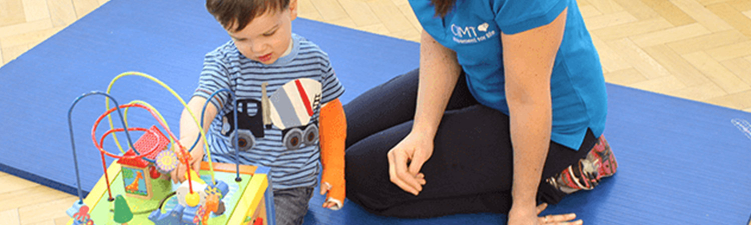 CIMT child playing with a bead train toy with their personal physiotherapist
