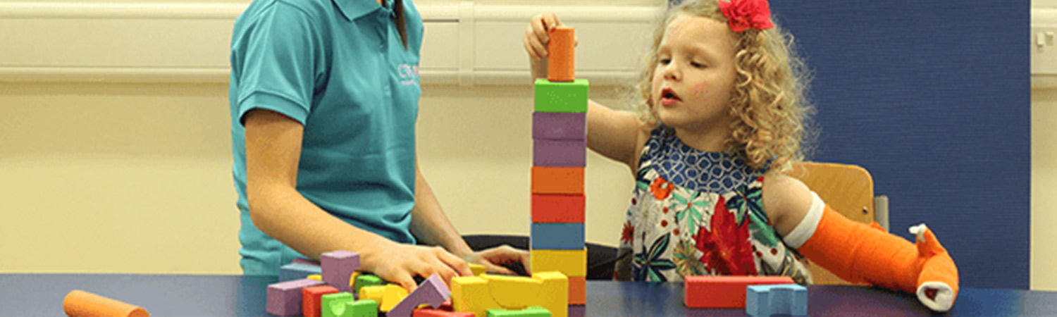 Child stacking blocks with her hand in a CIMT cast