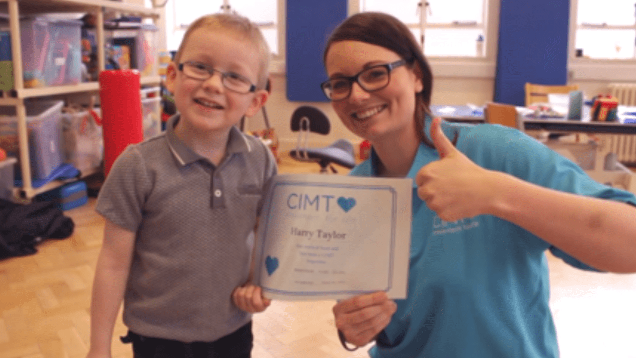 Harry smiling and holding a certificate with his CIMTuk therapist Nikki