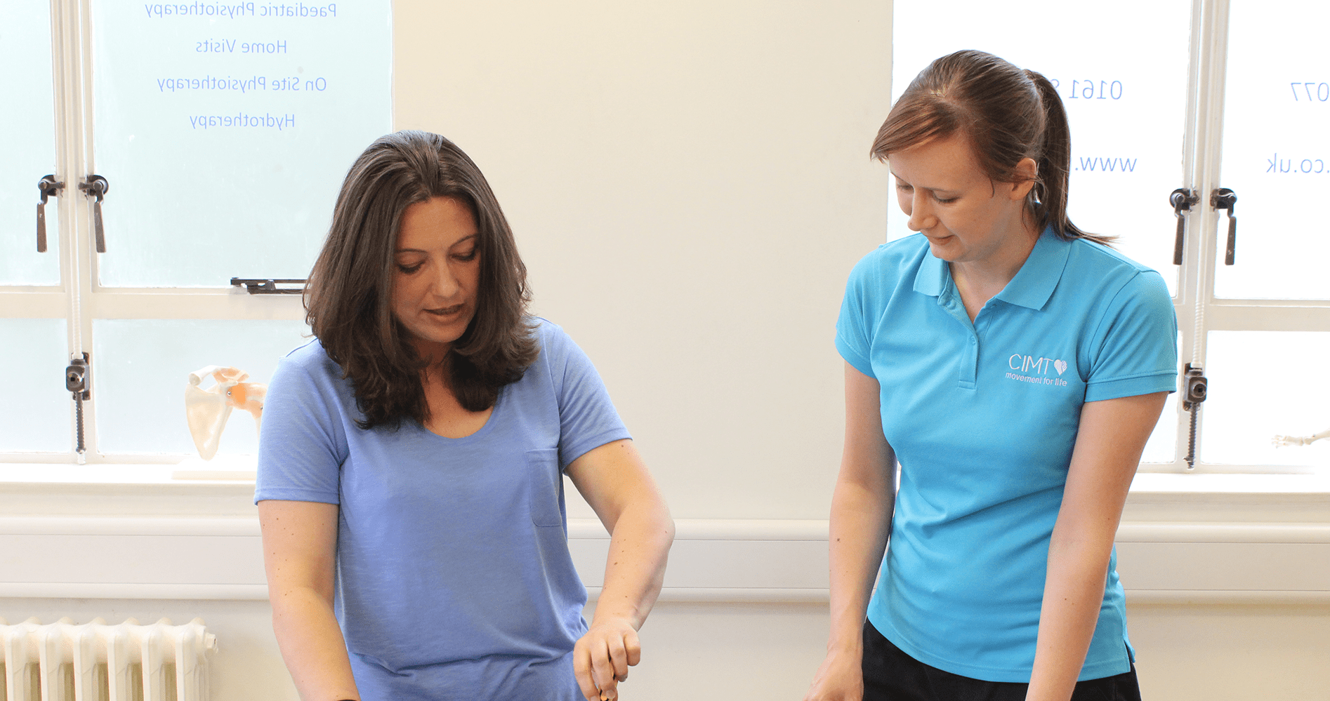 CIMT therapist aids adult woman during CIMT session at a clinic